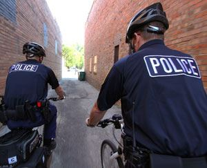 Two police officers riding police bikes down an alley.